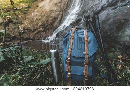 Hipster Blue Backpack Thermos And Trekking Poles Closeup. View From Front Tourist Traveler Bag On Waterfall Background. Adventure Hiking Concept