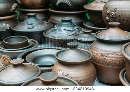 Many handmade brown clay pots, bowls, mugs. Ceramic clay, different kitchen utensils at shelf of street market