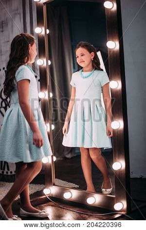 Cute Little Fashionista. Happy Child Girl Looking At Mirror.