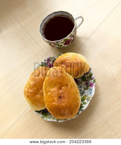 Fresh Only Baked Fluffy Hot Pies With Orange Crust Oiled Lie On A Thin Porcelain Saucer, Next To A C