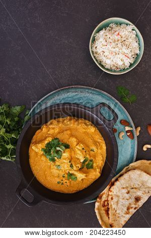 Chicken Korma, traditional Indian dish with nuts, jeera rice and naan bread on rustic surface. Top view, blank space