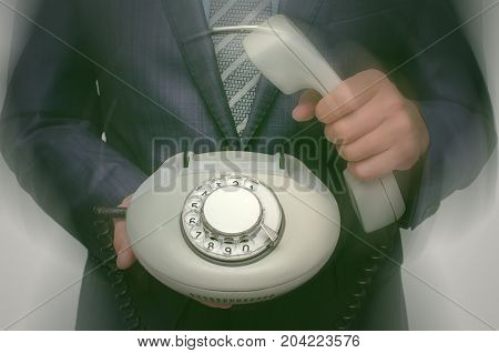 Blurred image of business man in suit holding analog phone handset in front of him. Contact us. Call us. Customer help service. Hot line consultant. Phone talk.