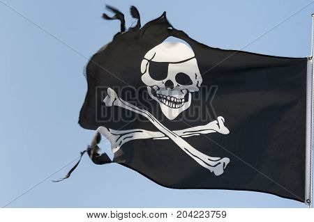 Torn pirate flag against the blue sky