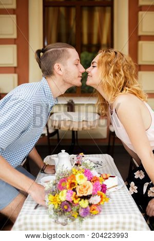 Happy young couple. Boyfriend and girlfriend sitting in cafe in the daytime while looking into each other's eyes. Beautiful woman is going to kiss her beloved