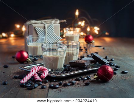 Homemade baileys or coffee liqueur in shot glasses roasted coffee beans and chocolate Christmas decoration holidays selective focus toned image