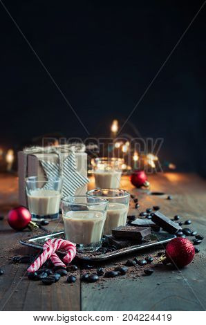 Homemade baileys or coffee liqueur in shot glasses roasted coffee beans and chocolate Christmas decoration holidays selective focus toned image copy space
