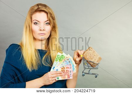 Happy woman holding shopping basket with bread holding money thinking about prices.