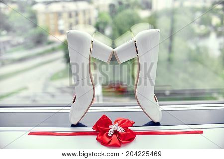 Bride Shoes And Garter On The Bride Window. Preparing For A Wedding Ceremony