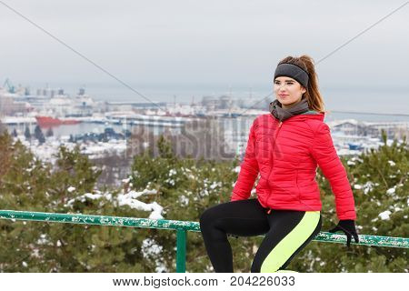 Outdoor sport exercises sporty outfit ideas. Woman wearing warm sportswear relaxing after exercising outside during winter. Panorama cityscape in background.