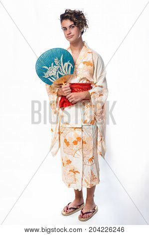 Teen age girl dressed in casual Japanese Yukata kimono holding paper fan on shoulder.