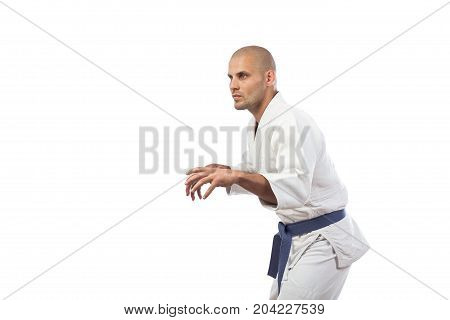 A young athletic man is a fighter in a white kimono for judo jiu jitsu sambo with a blue belt standing in a fighting rack on a white insulated background