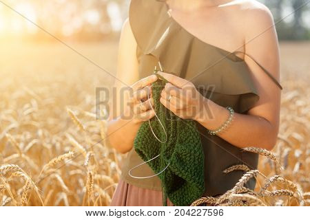 close-up of a young woman in a green romantic top knits with knitted natural woolen threads of a green sweater in a wheat field on a summer day in the background a green forest