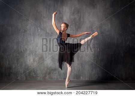 Young beautiful ballet dancer with gathered hair in a bun in a black dress pointe shoes smiling and beautifully dancing ballet in a dark dance studioYoung beautiful ballet dancer with gathered hair in a bun in a black dress pointe shoes smiling and beauti