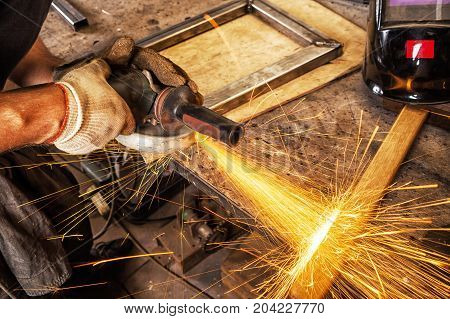 Close-up on the sides fly bright sparks from the welding machine. A young male welder in working gloves grinds a metal product with angle grinder in the garage
