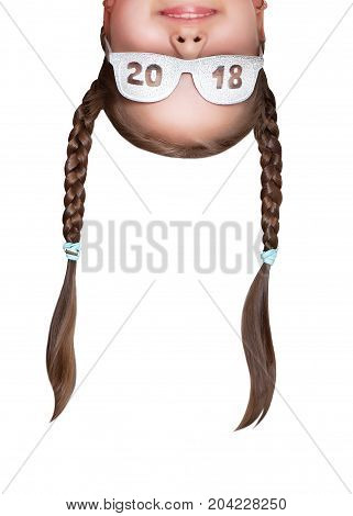 Funny girl with pigtails wearing glasses with an inscription 2018 upside down. Head portrait closeup.
