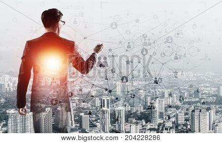 Double exposure of elegant businessman with pen in hand looking away