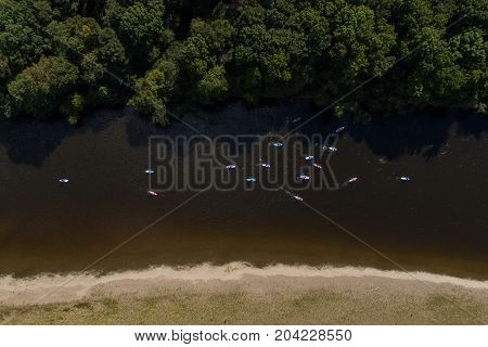 SUP unidentifiable people paddle boarding on a calm river during summer view from the drone