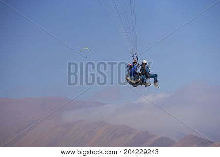 Iquique, Tarapaca Region, Chile - August 20, 2017: Tandem paragliding over the coastal city of Iquique on the northern coast of Chile.