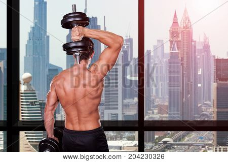 Shirtless Muscular Man Exercising With Dumbbell Standing In Front Of Window Inside The Gym