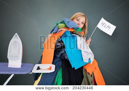 Woman Holding Help Flag With Huge Pile Of Laundry For Ironing Against Gray Background