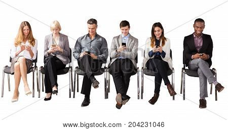 Group Of Multi Ethnic Business People Sitting On Chair Using Cell Phone Against White Background