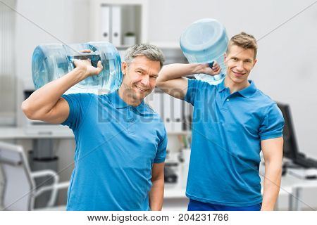 Portrait Of Two Smiling Delivery Men In Uniform Carrying Large Water Bottle