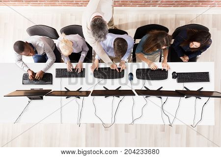 Elevated View Of Male Teacher Assisting Students In Computer Room
