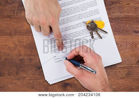 High Angle View Of A Real Estate Agent's Hand Helping Client In Filling Contract Form