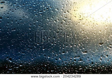 Rainy wet cold sky eco seasonal natural abstract background with water drops and sun spot