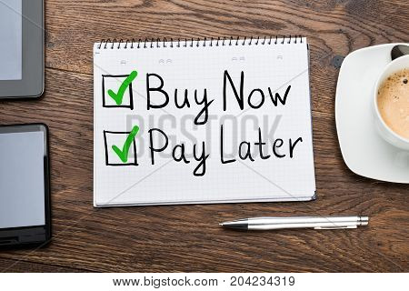 Buy Now Pay Later Concept In Notepad At Desk