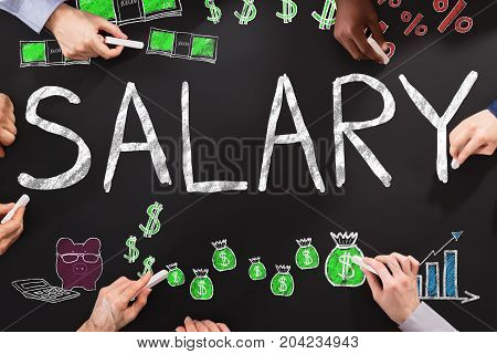 Hands Drawing Salary Word On Black Blackboard