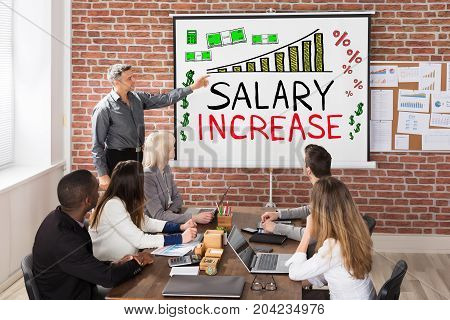 Man Giving Salary Increase Presentation To Colleagues