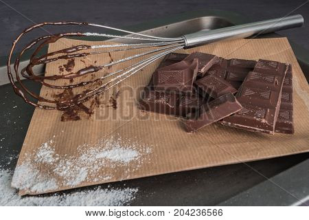 Chocolate chunks. Chocolate bar pieces and whisk on board.