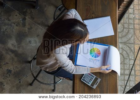 Young asian manager checking the income of company last month