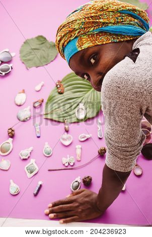 one young afro american woman looking at camera looking behind jewelry pendants objects laying on paper background colorful