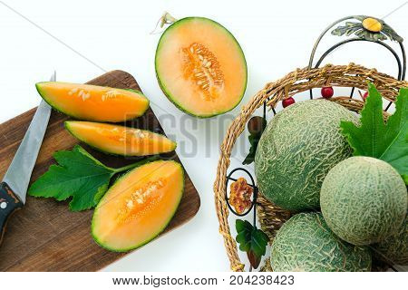 Ripe Melons Cut Into Pieces On A Wooden Board. Whole Melons In The Basket. White Background. Selecti