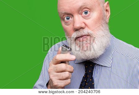 Elderly man is speaking to voice recorder on green background color and contrast manipulated