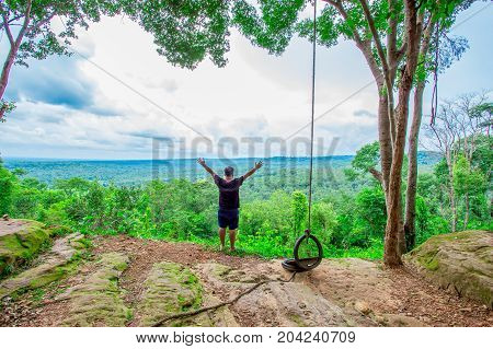 Man on peak of mountain. Emotional scene. Young man with backpack standing with raised hands on top of a mountain and enjoying mountain view. Hiker on the mountain top. Sport and active life concept