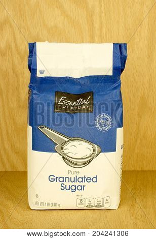 RIVER FALLS,WISCONSIN-SEPTEMBER 14,2017: A four pound bag of granulated sugar with a wood background.