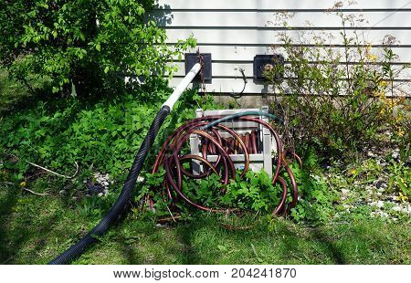 Garden hoses, and a hose leading from a sump pump, lie behind a tract home in Joliet, Illinois during April.