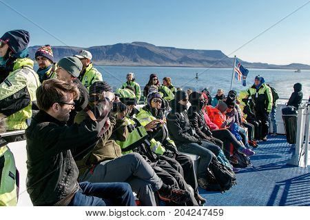 Reykjavik Iceland August 20 2017: People wearing warm overalls are riding a boat during a whale watching tour on a sunny afternoon.