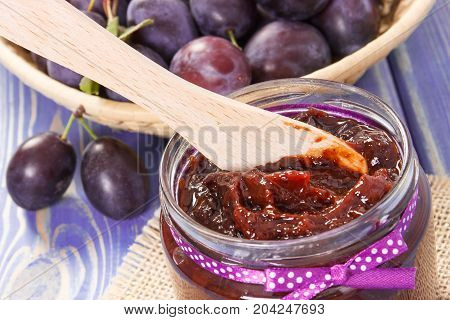 Wooden Knife And Plum Marmalade Or Jam In Glass Jar, Healthy Sweet Snack Or Breakfast Concept