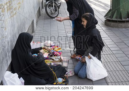 Tehran IRAN - September 3 2017 Street photography muslim woman weave loofah with yellow yarn in pavement and selling them to passengers.