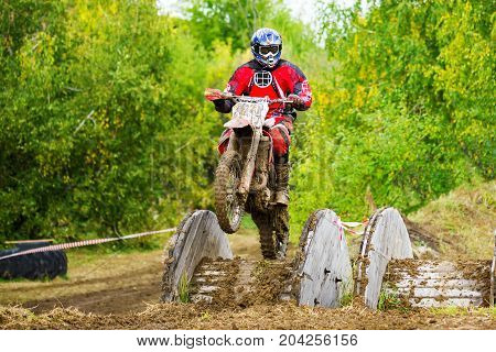 Motorcycle off-road cross competition on a muddy track with obstacles. The emblem on the chest of the rider is changed