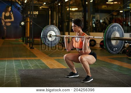 Young Vietnamese sportswoman doing heavy duty squats with barbell