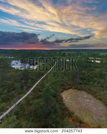 Aerial view on wooden footpath through Suru Suursoo bog after sunset Estonia