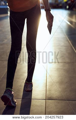 close up legs of young woman in the hall of the airport terminal with a passport and boarding pass. silhouette of a woman in a bracing light. woman waiting for her flight on background blur airport check-In counters and passenger.