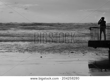 Back view of a tourist taking photo of sea storm with smartphone in front sea in black and white