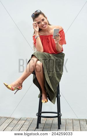 Pretty laughing young woman with a phone sitting on chair