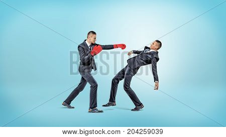 A businessman in boxing gloves fails to punch another man who manages to avoid the kick. Fierce competition. Business rivals. Overcome yourself.